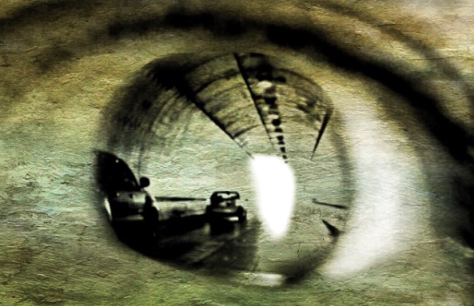 Double exposure showing an image of cars moving toward the light at the end of a tunnel overlaid over a closeup of Luis's eye.